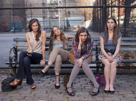 Cast of Girls sitting on a bench